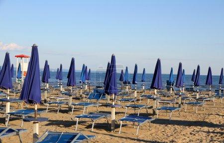 Photo pour Beaucoup de parasols et de transats sur la plage au coucher du soleil sur le bord de la mer avec la tour de guet - image libre de droit