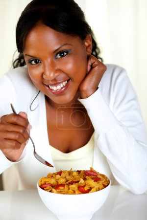 Photo for Portrait of a relaxed woman looking at you and having breakfast at soft colors composition - Royalty Free Image
