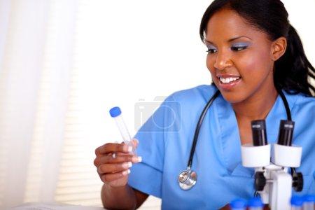 Photo pour Belle infirmière avec un stéthoscope en uniforme bleu, travaillant au laboratoire - fond - image libre de droit