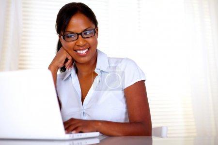 Afro-american secretary reading on laptop screen