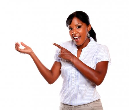 Surprised young woman pointing to her right hand