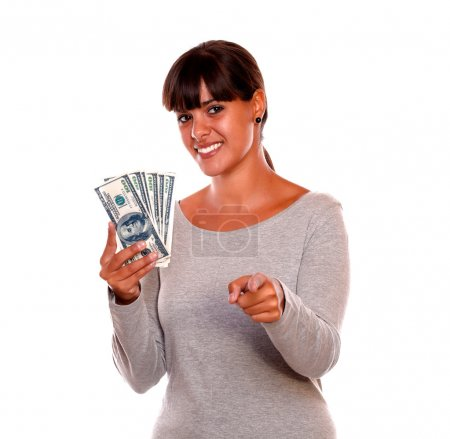Smiling young woman with money pointing at you