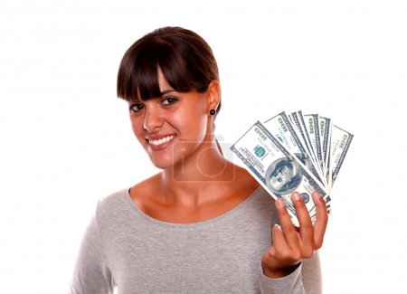 Smiling pretty young woman holding dollars