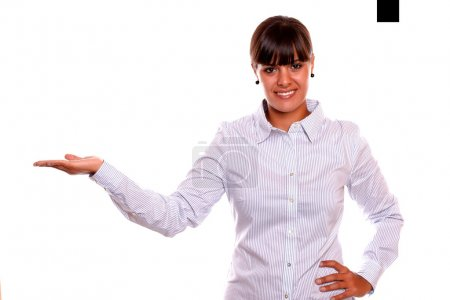 Photo for Portrait of a smiling young business female holding out her right palm and showing you copyspace on white background - Royalty Free Image