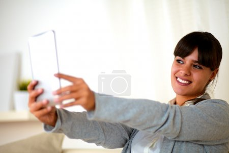 Young woman taking a photo with tablet pc