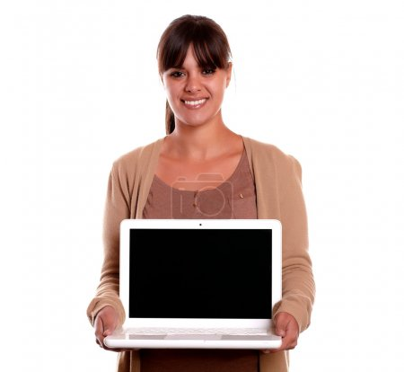Charming young woman showing at you laptop screen