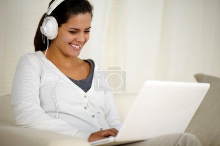 Photo pour Portrait d'une jeune femme souriante avec casque d'écoute de musique tandis que parcourt l'internet sur ordinateur portable à la maison intérieure - image libre de droit