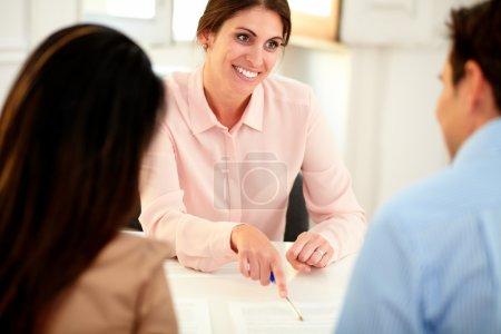 Photo pour Portrait d'une charmante conseillère financière lors d'une rencontre avec un jeune couple tout en souriant et assis au bureau de la banque - image libre de droit