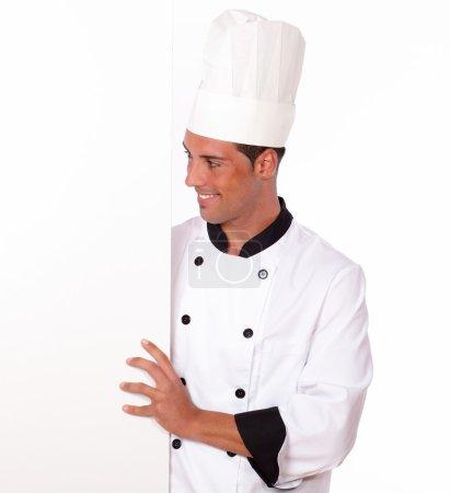 Photo pour Portrait d'un beau chef en uniforme blanc tenant une pancarte blanche vierge debout sur un fond isolé - copyspace - image libre de droit