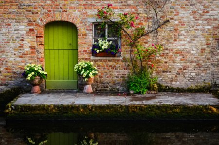 Vintage old wall with green door and flowers