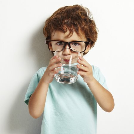 Photo for Portrait of boy drinking glass of water isolated in white - Royalty Free Image