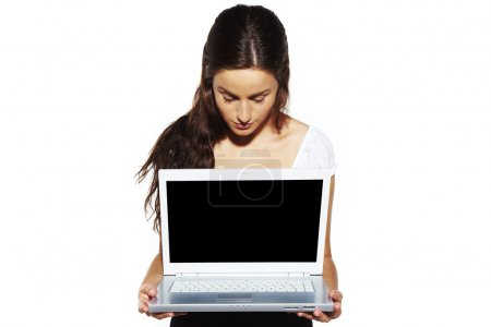 Portrait of a young girl presenting laptop...