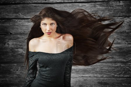 Young brunette woman with long flying hair, over wood background