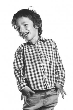 Laughing child with hands in pockets. Black and white colors.