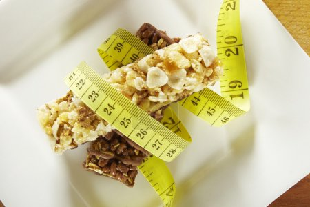 Cereals and chocolate bars with measuring tape in a dish