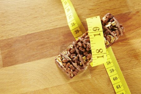 Chocolate muesli bar measuring tape on wooden background