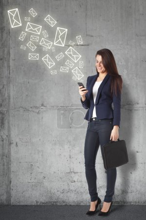 Beautiful businesswoman sending a message on smartphone