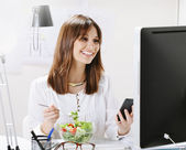 Young woman creative designer eating a salad while working in office.