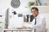 Young businessman in office looking at camera.