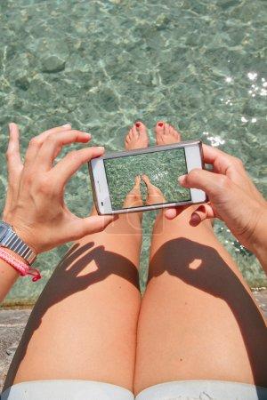 Photo pour Jeune femme prenant des photos de ses jambes . - image libre de droit