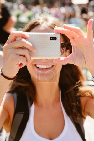 Beautiful young woman taking photos with mobile phone.
