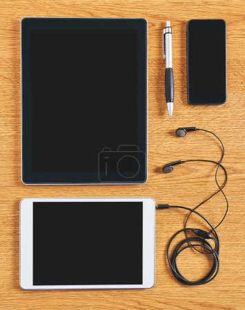 Composition of tablet, phone and headphones on a desk.