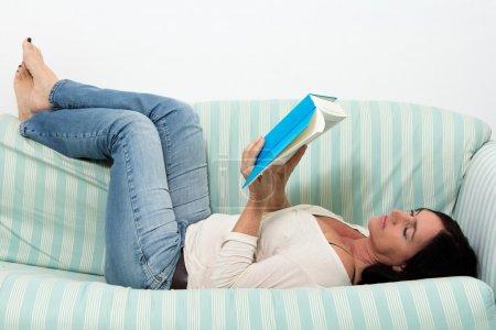 Photo pour Femme aux cheveux foncés allongée sur le canapé et lisant un livre bleu - image libre de droit