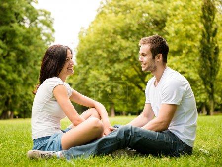 Foto de Joven pareja feliz hablando juntos al aire libre - sentado en el césped - Imagen libre de derechos