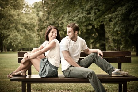 Photo for Young smiling couple looking on each other - sitting on bench - Royalty Free Image