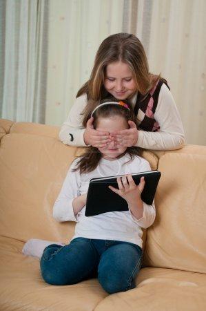 Photo pour Un enfant joue avec la tablette sur le canapé tandis que l'autre fille couvre ses yeux - image libre de droit