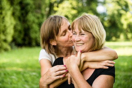 Photo for Adult daughter kissing her smiling happy senior mother - outdoor in nature - Royalty Free Image