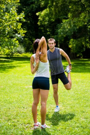 Young man and woman exercising and stretching musc...