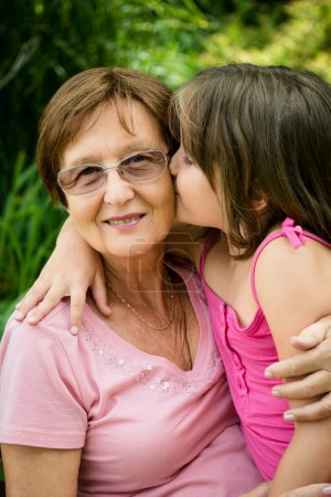 Photo for Lifestyle portrait of grandchild kissing grandmother - outdoor in nature - Royalty Free Image