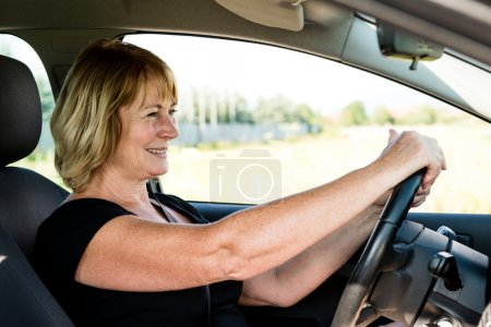 Photo for Lifestyle photo of attractive senior woman driving car - Royalty Free Image