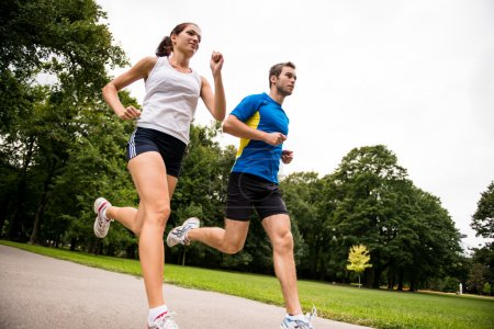 Low angle photo of young couple jogging outdoor in...