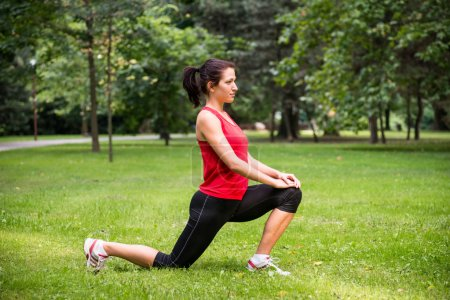Photo for Young sport woman exercising before jogging - outside in nature - Royalty Free Image