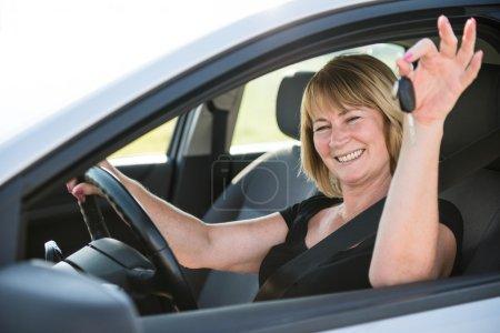 Photo pour Portrait d'une séduisante femme souriante tenant les clés d'une voiture neuve - image libre de droit