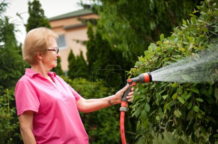 Senior woman watering garden