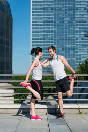 Photo for Sport couple exercising and stretching muscles before jogging activity in city - Royalty Free Image