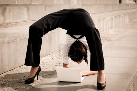 Flexible business - woman with laptop exercising...