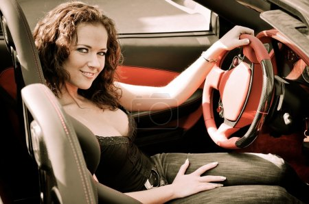 Photo for Young beautiful happy woman in sport car holding steering wheel - red interior detail - Royalty Free Image