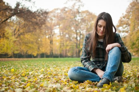 Photo for Portrait of young worried person siting in depression outdoor in fallen leaves - Royalty Free Image