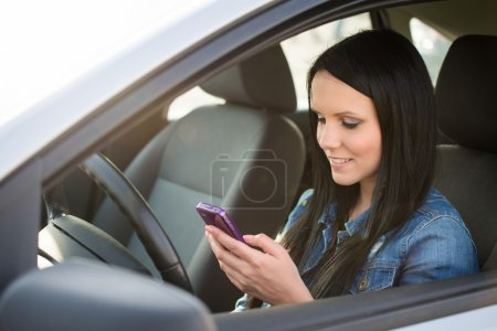 Young beautiful woman using smartphone while drivi...