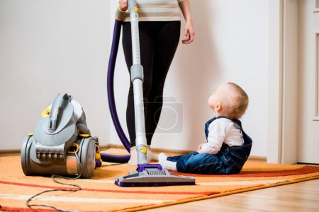 Cleaning up the room - woman with vacuum cleaner, ...