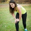 Sport injury - young fitness woman holding her kne...
