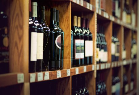 Photo for Wine bottles on wooden shelf in wine store - Royalty Free Image