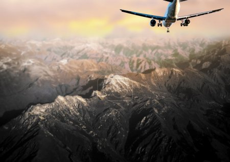Passenger aircraft over mountain landscape at dawn...