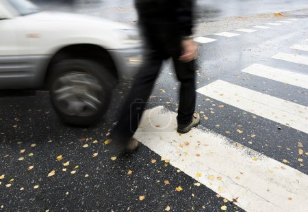 Photo for Man on pedestrian crossing in autumn, in danger of being hit by car - Royalty Free Image