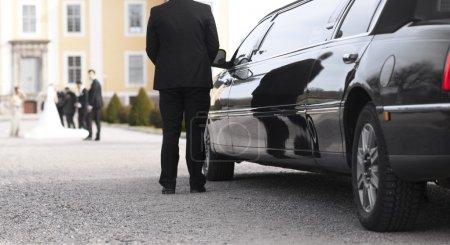 Photo pour Limousine noire avec chauffeur attendant mariée et marié devant le manoir - image libre de droit