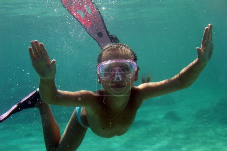 Girl swimming underwater with diving mask